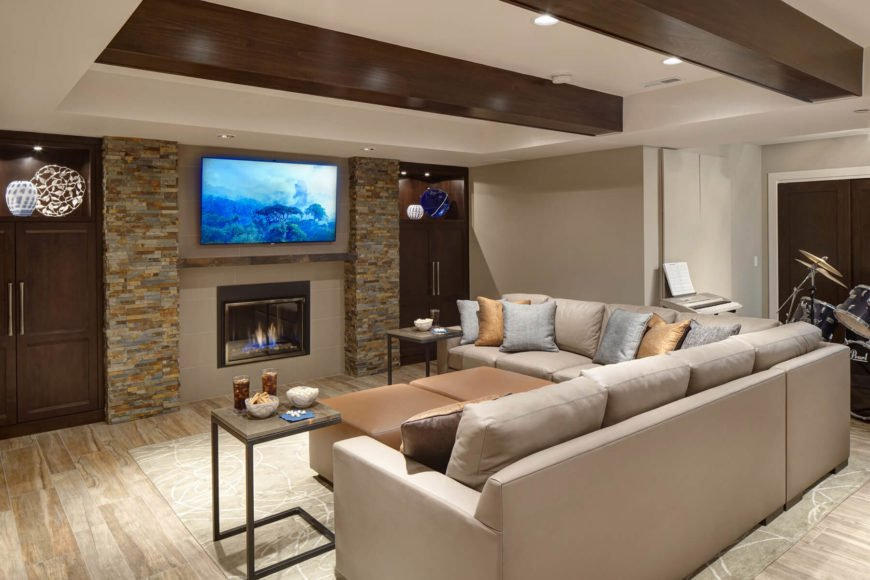 The seating area wraps the large leather sectional, holding silver and gold throw pillows, around a pair of cubic tan ottomans. recessed lighting in ceiling and cabinetry subtly illuminates the space.