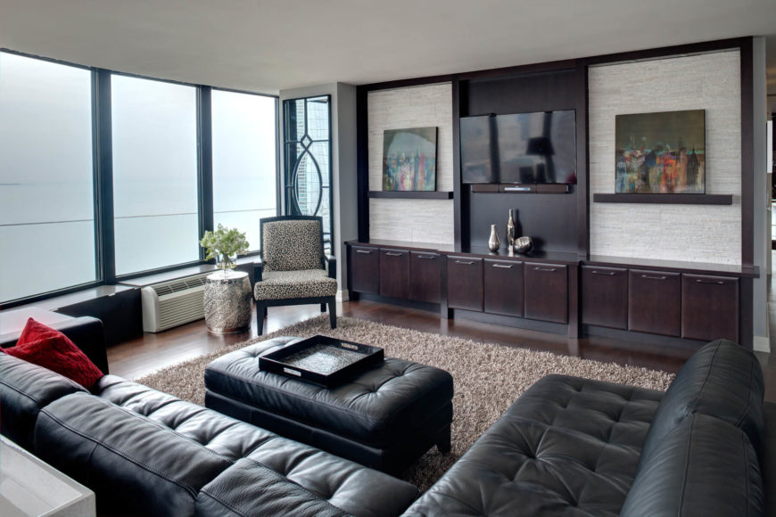 Sumptuous button tufted black leather sectional wraps this family room, flaunting hardwood flooring, dark wood wall-length shelving, and a brown shag area rug. Floor to ceiling windows brighten the space.