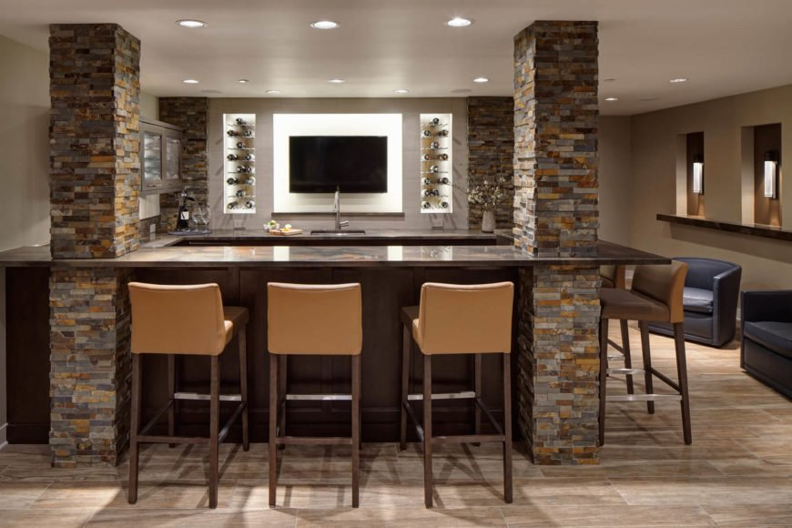 The fully equipped bar space involves dark maple wood and quartzite countertops framed by four stone brick columns. An array of tan leather bar stools are supplemented by contemporary blue armchairs at right.
