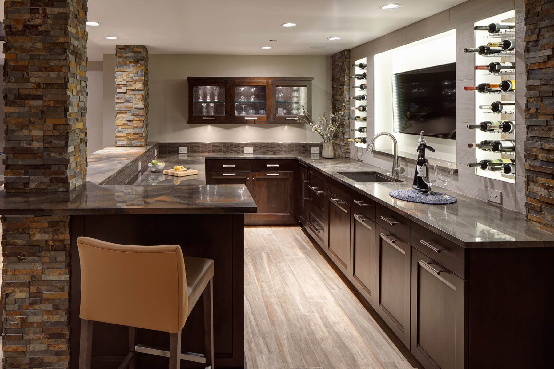 The bar cabinetry features stainless hardware beneath quartzite countertops, while sink is backed by a recessed television cove, flanked by inner-lit wine shelving. Glassware can be seen behind rippled glass panel upper cabinet doors.