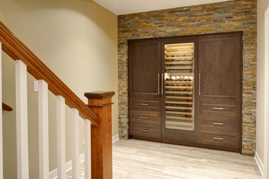 The basement features a full fledged wine storage unit with more of the dark stained maple, set into a wall of the stonework. Internal lighting makes for a grand display.