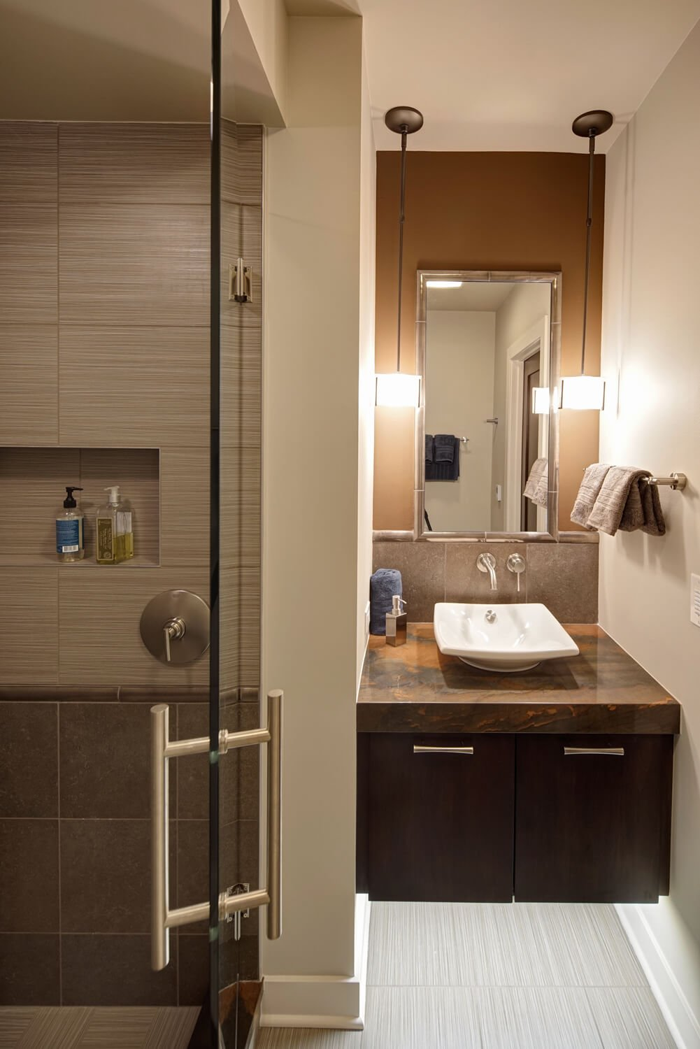 The basement holds its own private bathroom space, with floating marble topped vanity lit from beneath. Vessel sink and wall-mounted faucet enhance the modern feel, as does the glass enclosed shower at left.
