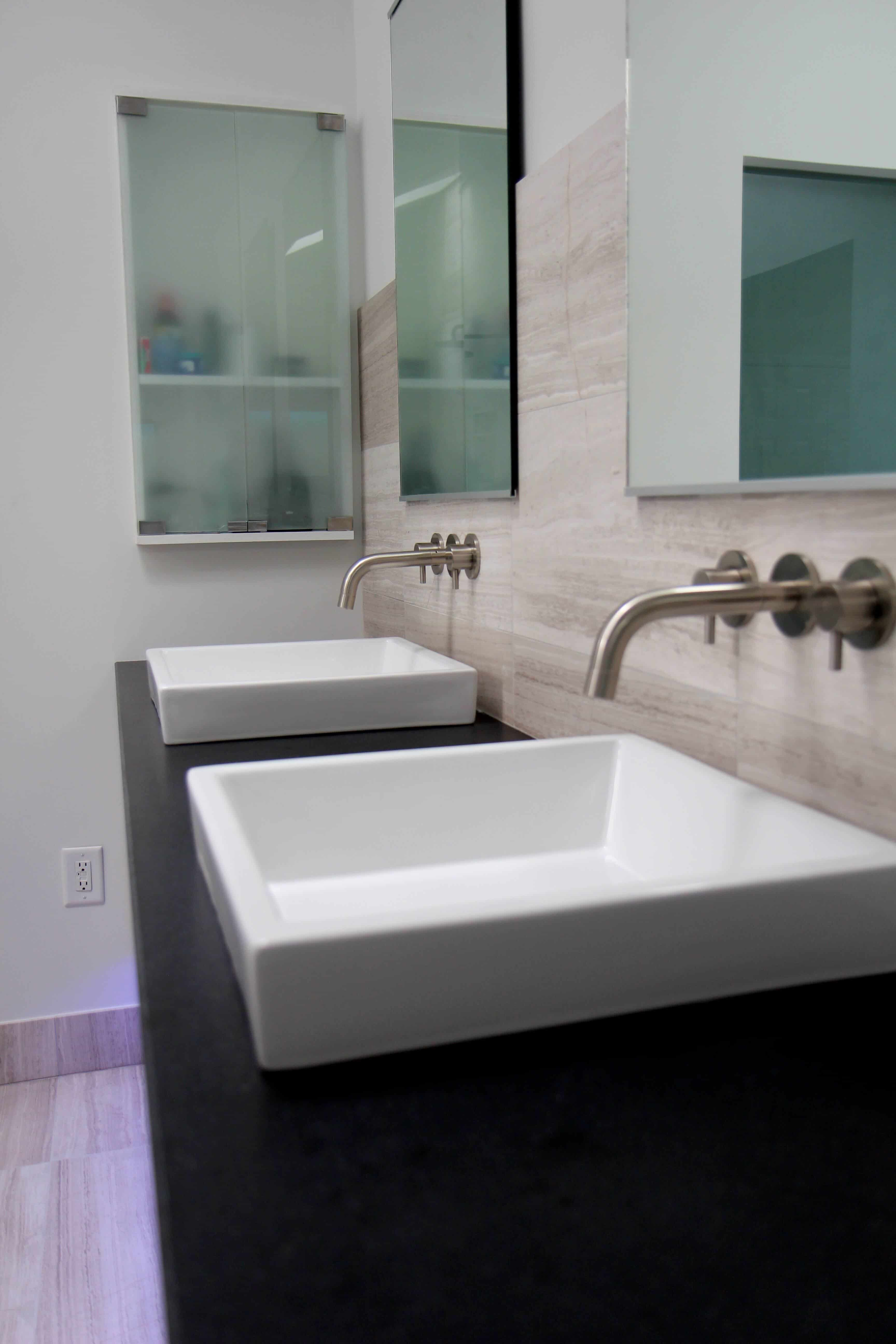 A closer look at the dual vessel sinks with faucets extending from the tile backsplash. Each sink has its own mirror above it.