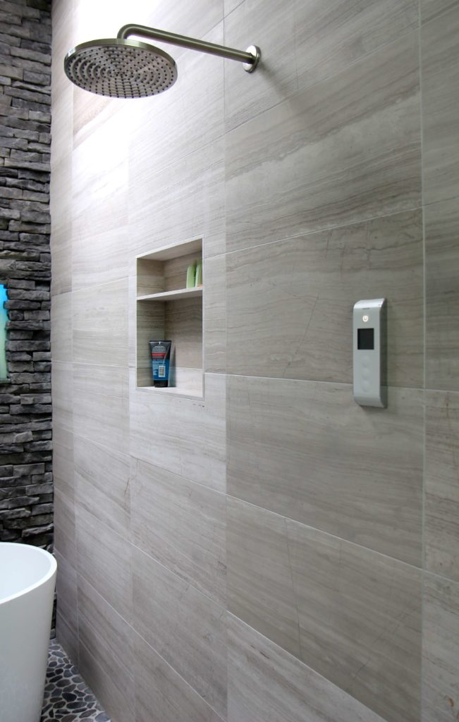 A closer look at the other side of the shower shows another brushed nickle shower head, a digital shower valve, and yet another cubby for shower products.