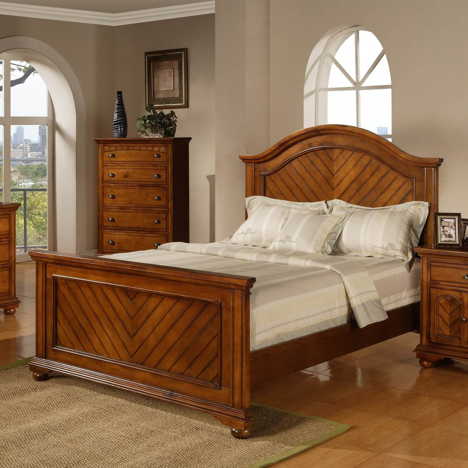 A panel bed consists of a headboard and footboard made from flat panels of wood. The panels are framed with raised molding or grooves that mimic traditional wood paneling or wainscoting. The headboard and footboard are connected by wooden rails.