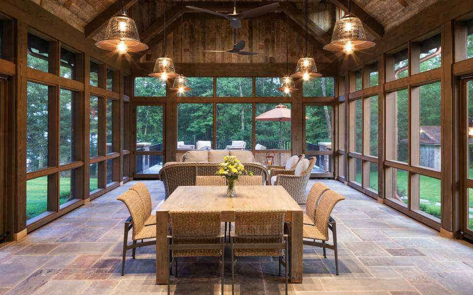 This enclosed, patio-like room stands a floor to ceiling window wrapped space beneath a natural wood exposed beam ceiling, with six bell chandeliers illuminating a dining set and sofas in resin wicker. Stone tile flooring reflects the exterior stone.