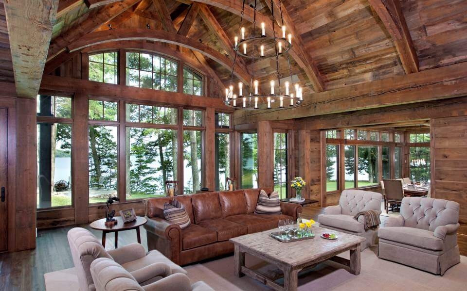 The grand living room sits beneath a high vaulted ceiling with arched, exposed wood beams. The natural upper wood meets lightly stained wood framing the immense wall-size windows, while a two-tiered iron chandelier hangs at center.