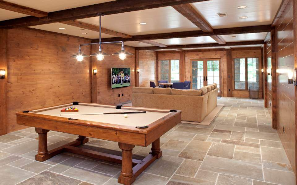 This space contrasts with the upper level, featuring stone tile flooring and glossy wood wall textures, with exposed beams running end to end on a light toned hardwood ceiling. Full natural wood pool table stands below a metal pipe style light.