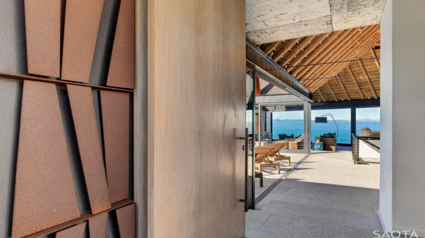 Through the main entrance, we see the mixture of wood, stone, and structural I-beams framing the interior. Glass exteriors throughout highlight the spectacular views.