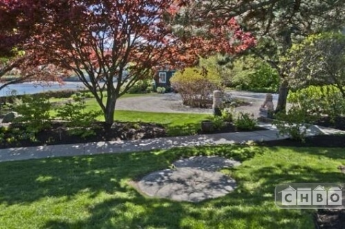 The manicured front garden has a stone walkway that winds through the property and is shaded by ornamental and native trees.