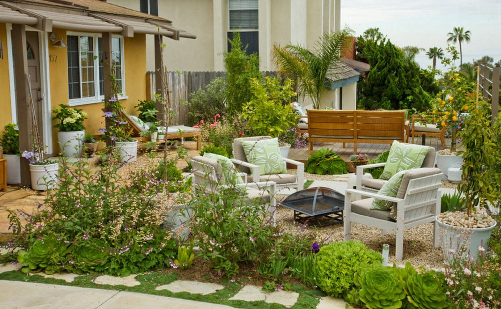 Four white chairs surround a small firepit on top of a pebble patio. The overall garden is bursting with shades of greenery, including succulents and shrubs, along with small flowering trees in planters.