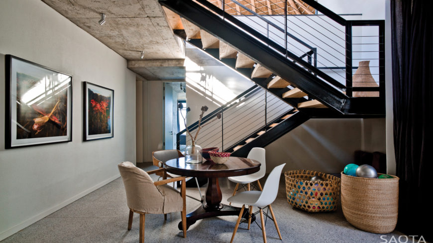 From the lower level, we see the central I-beam framed staircase. A small dining area in this open space gives way to hallways leading to the private bedroom areas.