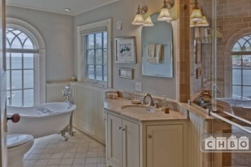This bathroom has a glass-enclosed shower stall, a claw foot bathtub and tile work on the floor and in the shower enclosure.