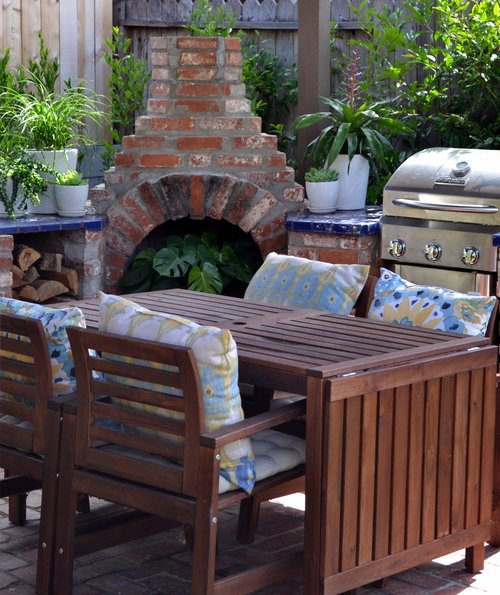 An old stone fireplace can be used for its original purpose or to house a small potted plant. The table is extendable, and a small grill rounds out the area.