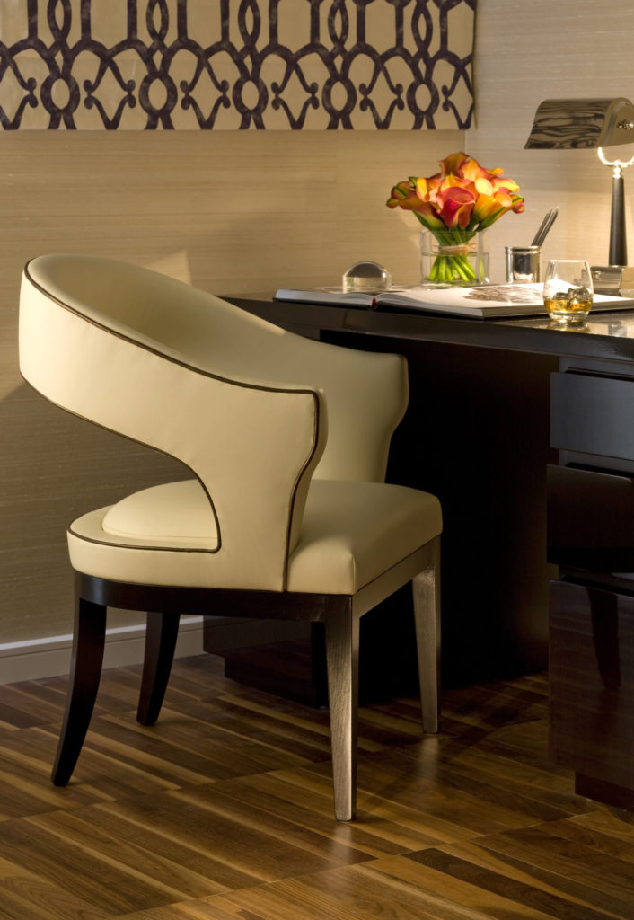 A small corner office space is staked out by this rich, dark wood desk and contemporary cream leather accent chair.