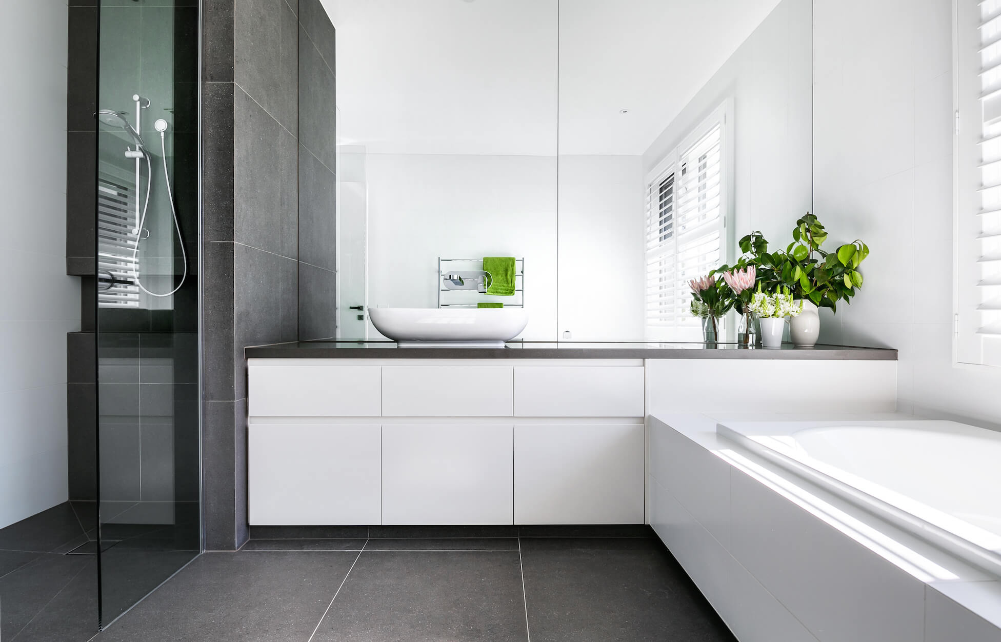 This secondary bathroom features another vessel sink, standing here between a large window seat soaking tub and glass enclosed walk-in shower.