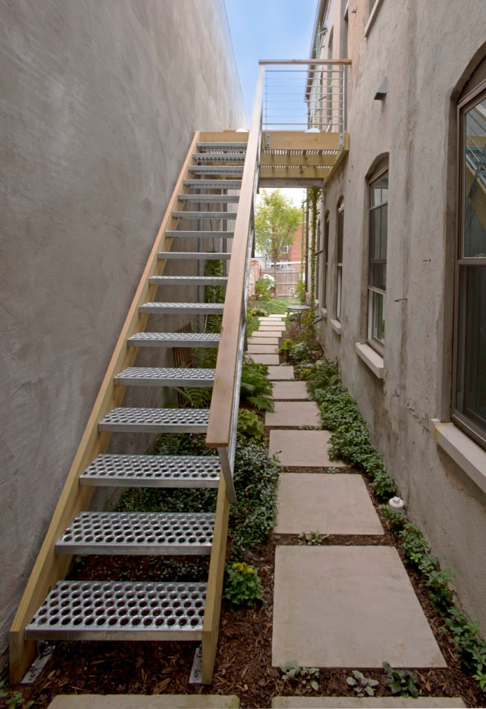 At the foot of the stairs, a stone and bark path, lined with small, easy to care for plants, leads into the backyard.