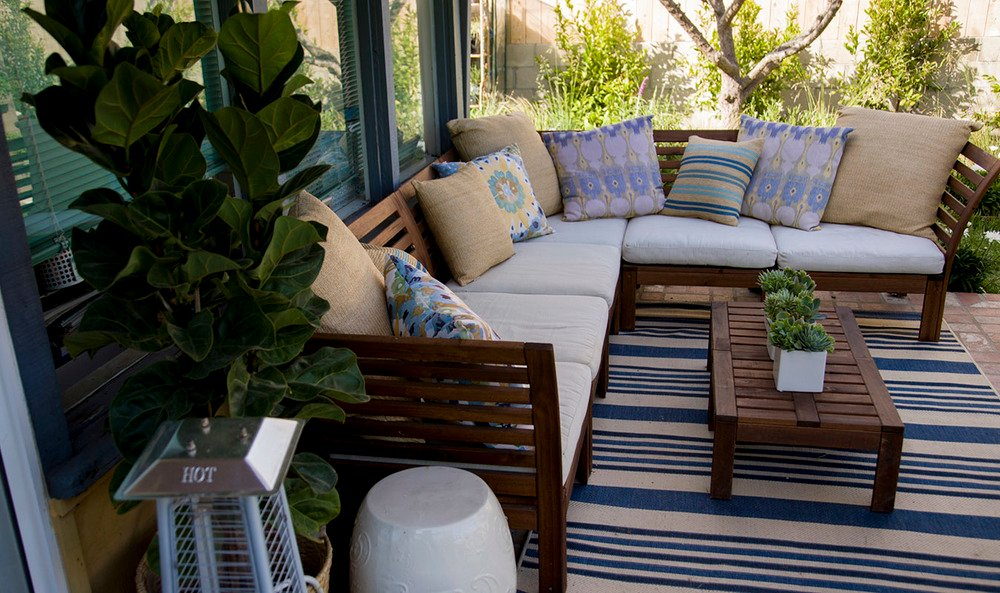An L-shaped sectional sofa rests on top of a blue striped rug, which warms the stone patio. Small succulents make another appearance as a centerpiece for the coffee table.