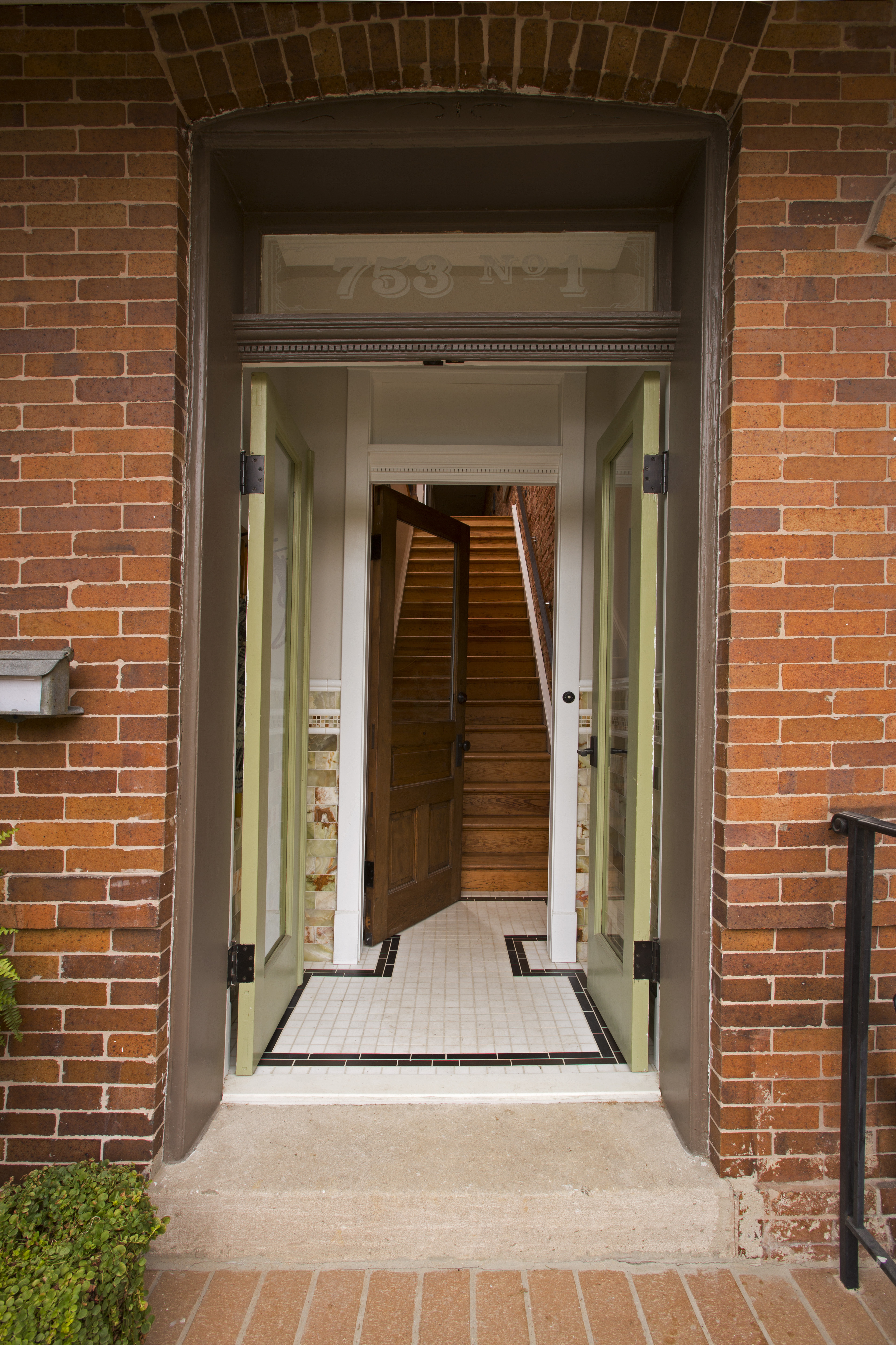 The green double doors lead into the main hardwood staircase to the first of the two condos.
