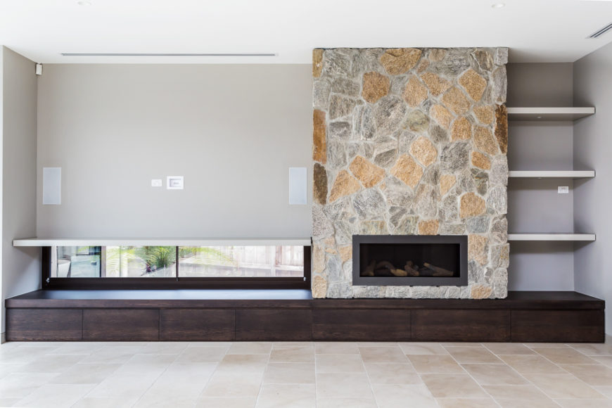 The living room features this massive stone surround fireplace over a dark wood room-wide shelving unit. Low slung windows allow for subtle views to the outdoors.