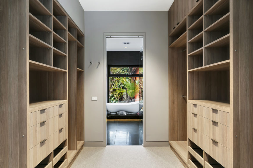 A large walk-in closet leading to the primary bath is flanked by floor to ceiling natural wood cabinetry.
