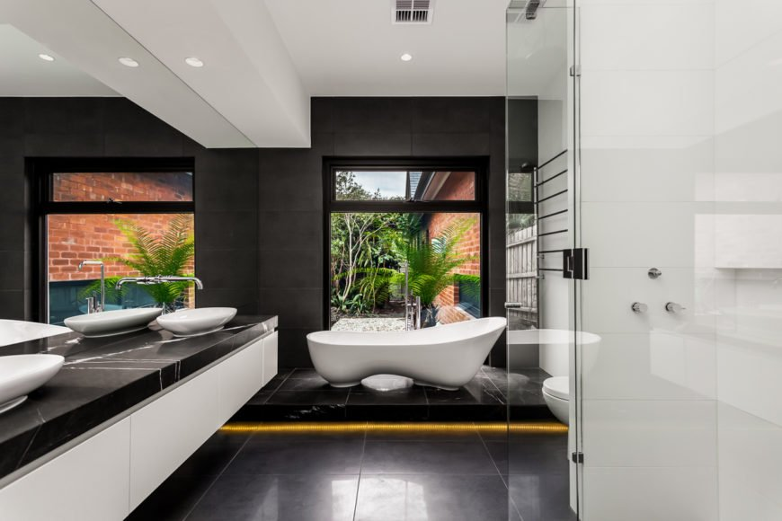 The primary bath is a stunning achievement, featuring high contrast between dark marble flooring, countertops, and walls, and the white vanity structure, vessel sinks, and unique oblong pedestal tub. Featuring a glass enclosure shower and large format window overlooking the garden, this is a boldly realized space.