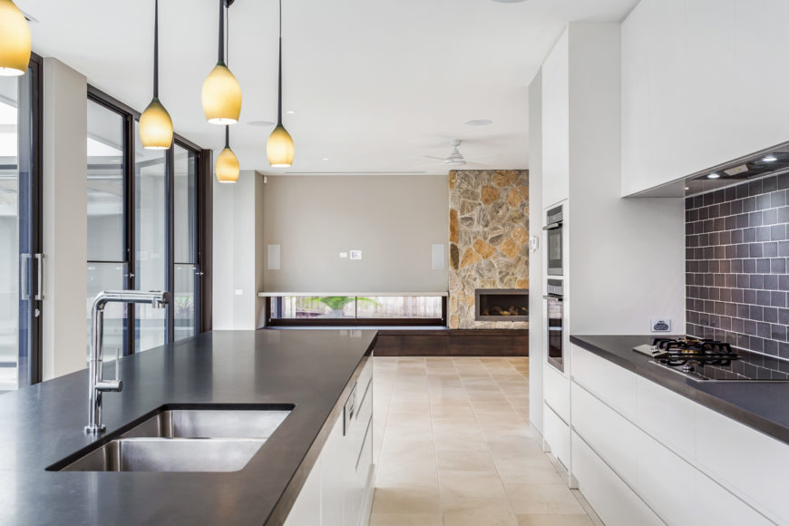 With a closer view, we see the high contrast mixture of sleek white cabinetry and black countertops defining the look of the kitchen, over the beige tile flooring shared by the entire central open space. Dark tile backsplash can be seen at right.