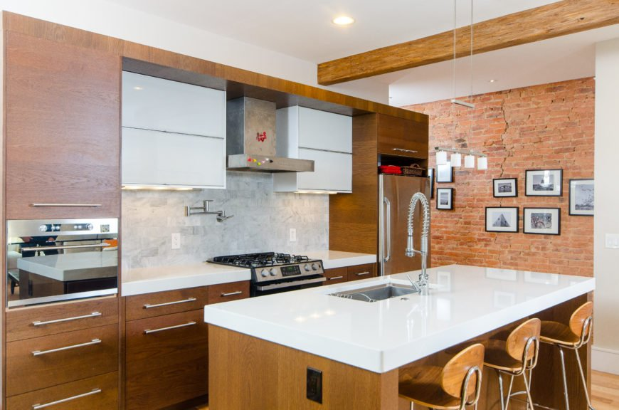 The sleek kitchen combines light wood cabinetry with bright white glossy countertops. Gray subway tiles make up the backsplash.