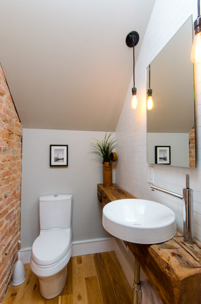 A third bathroom is more rustic in design, with a solid wood beam vanity and a vessel sink.
