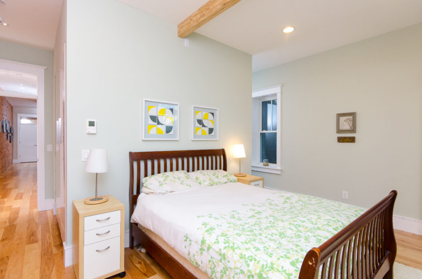 Another view of the bedroom shows the long hallway leading off to the left and the light pine hardwood flooring.