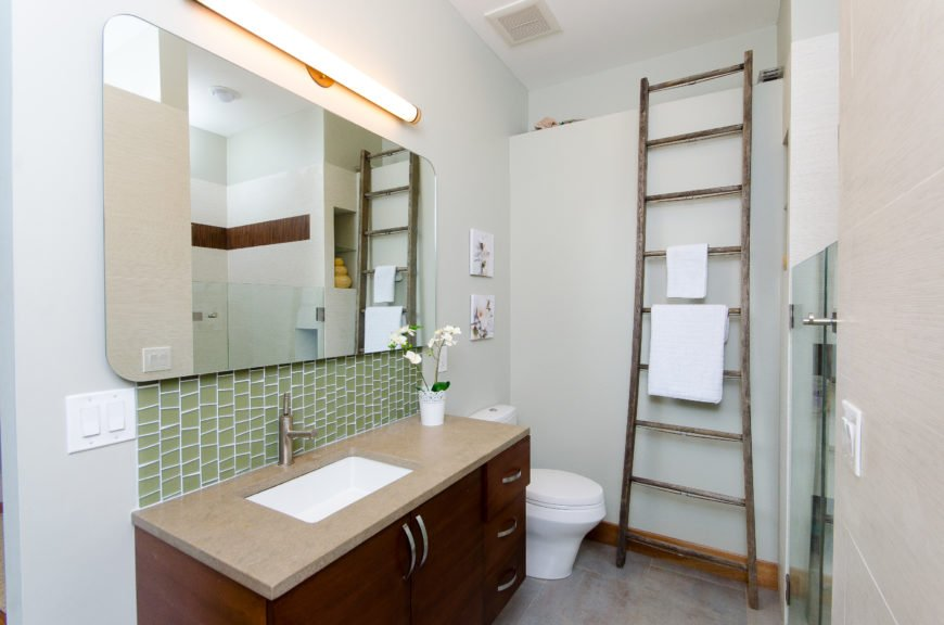 This bathroom combines a dark wood vanity with a simple sink and faucet with a large seamless mirror. An old wood ladder is repurposed as a towel rack.