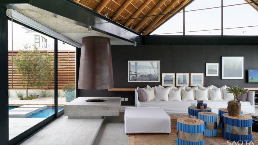 With a head on view, we see the lengthy sectional with its large ottoman detached, with cork stuffed stools nearby. The enclosed courtyard with pool can be seen at left, through windows below the large black I-beams.