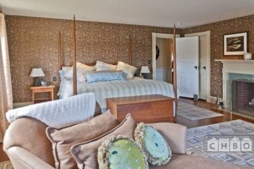 The primary bedroom combines stripes, florals, and geometric patterns with hardwood floors and recessed lighting around the perimeter of the room.