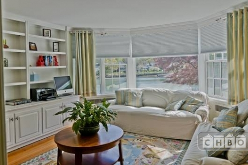 Another, smaller sitting room with a bay window and built-in shelving. Pastels in the rug and accent pillows add a soft pop of color to the white sofas and shelving.
