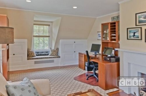 A small sitting room and study with a fireplace and window seat is a nice third floor retreat during the quiet hours of the day.