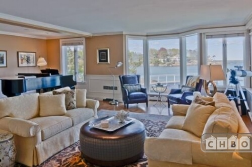 This living room is one of several, and contains the Steinway grand piano, a telescope and a view of the private dock. A circular ottoman sits between the two sofas and acts as a coffee table.