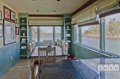 Off the kitchen is a small breakfast nook in pale blue. A bay window with a bench seat has two built-in shelving units on either side. Large Roman shades can be pulled down over the large windows for more privacy in the evening.