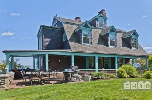 The exterior of the home has a gorgeous blue trim to brighten up the brown siding. A front patio sits near the front porch. The home sits on a large yard that includes gardens and manicured landscaping.