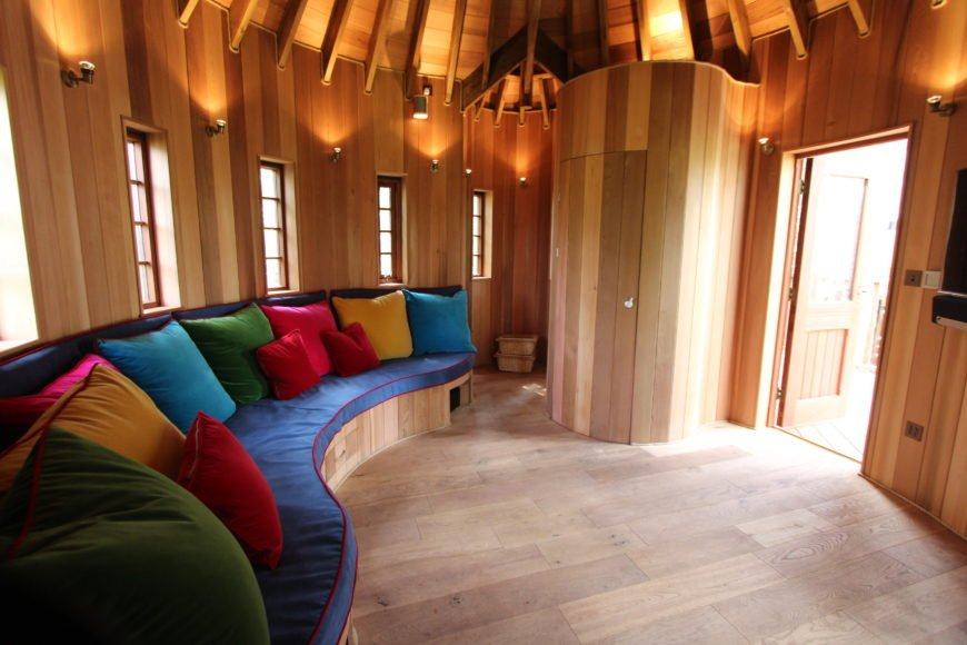 The cedar interior with many windows. A custom curved sofa is in bright primary colors. The floors are heated from beneath.