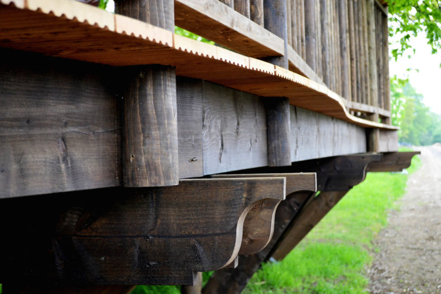 A close view of the deck structure reveals interlocking layers of wood, with bright oak planks forming the floor.