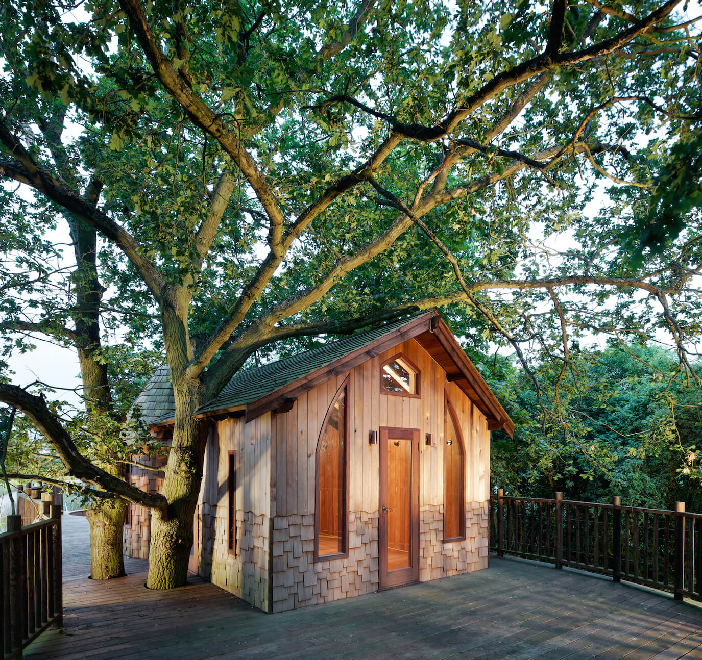 At the front entrance we see the rich cedar walls through full height windows flanking the glass panel door. The deck and roof itself are cut to wrap around the oak trees at left.
