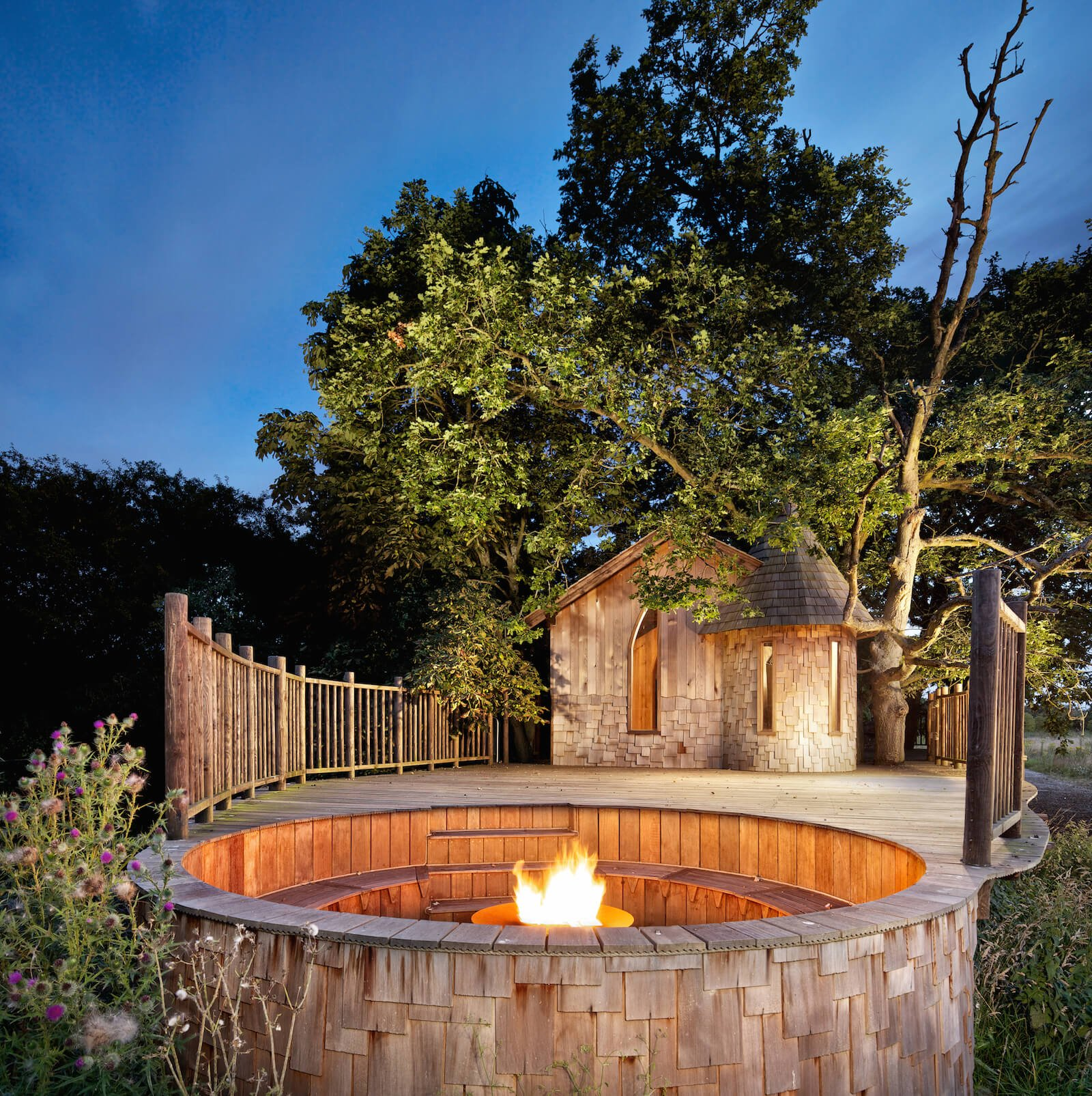 Finally, we leave you with this vision of the fire pit illuminated at night. The fencing gives way to this sunken conversation space, glowing beneath the trees.