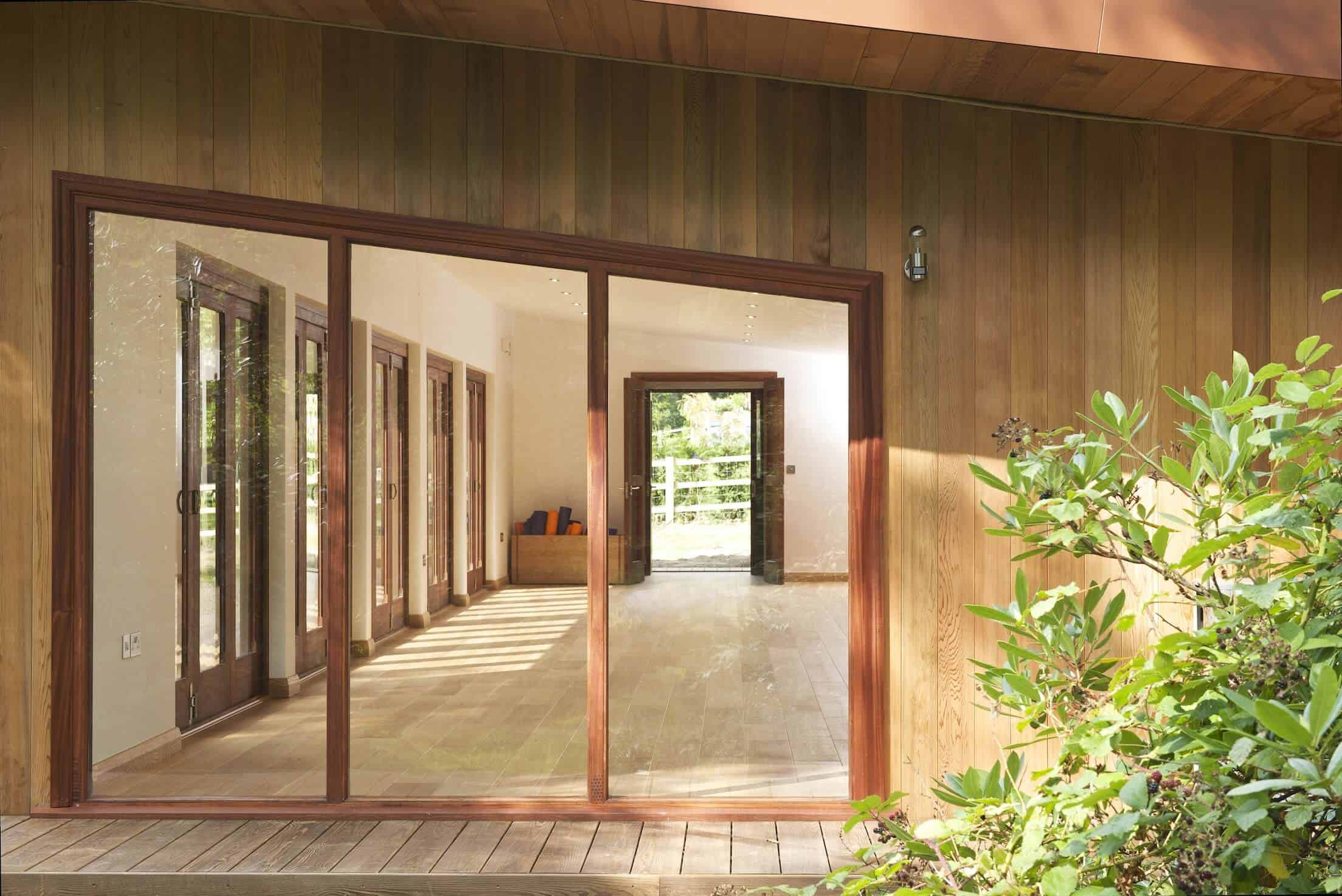 From the side, we see through full height windows clear across the studio, to a pair of doors at the opposite end.