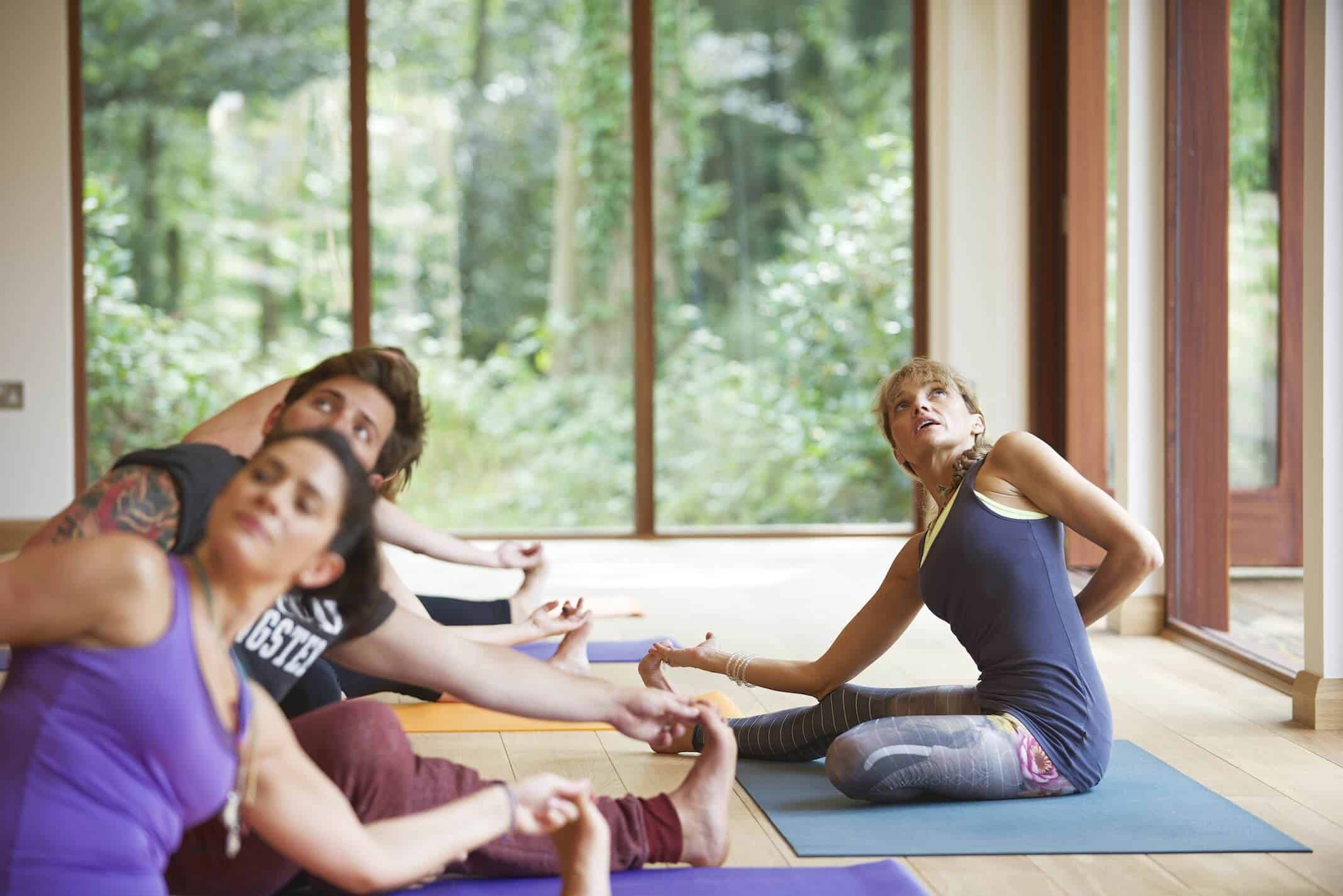 Here's another close focus shot of yoga in action in this warm, natural space. The surrounding forest is visible throughout the interior.