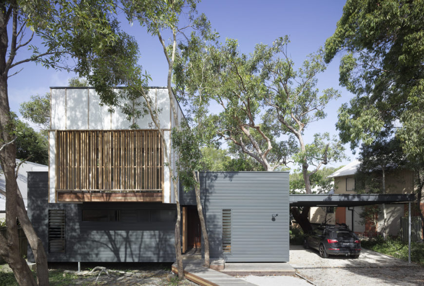 Seen from the street side, this minimalistic home obscures its striking design by hiding within the foliage, boasting a mixture of natural materials across the facade.