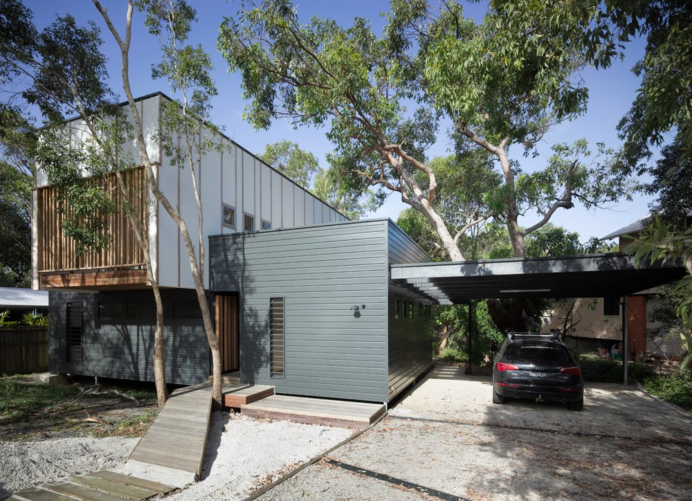A small natural wood path leads between a pair of trees to the front entryway. We see a mixture of materials, including grey wood cladding, white panels on the upper structure, and natural wood slats throughout.