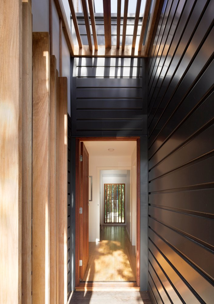 The central hall bisects the house, with a mixture of slatted wood openings and white interior walls. Natural light falls through skylights above.