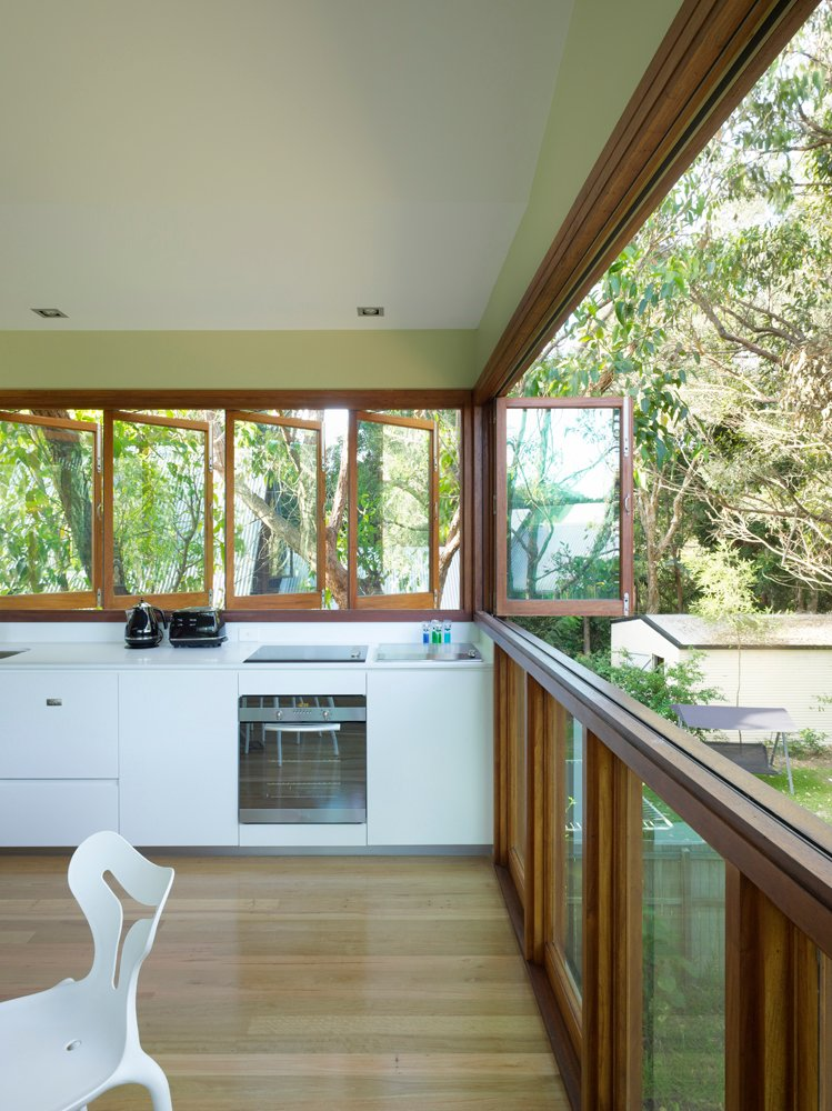 With the louvered windows fully opened, the space breathes with the outdoors, blurring the line between indoors and out. Wraparound views of the surrounding forest compliment the natural build materials.