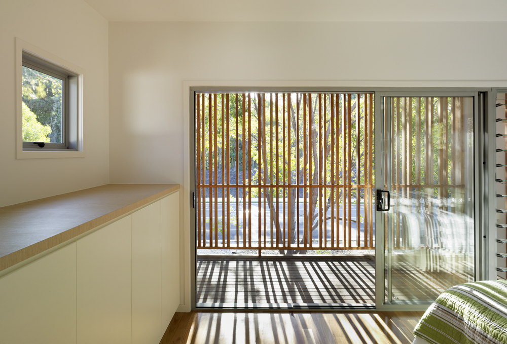 The primary bedroom opens through full height sliding glass to this semi-private balcony, with natural wood slats casting staggered shadows across the space.