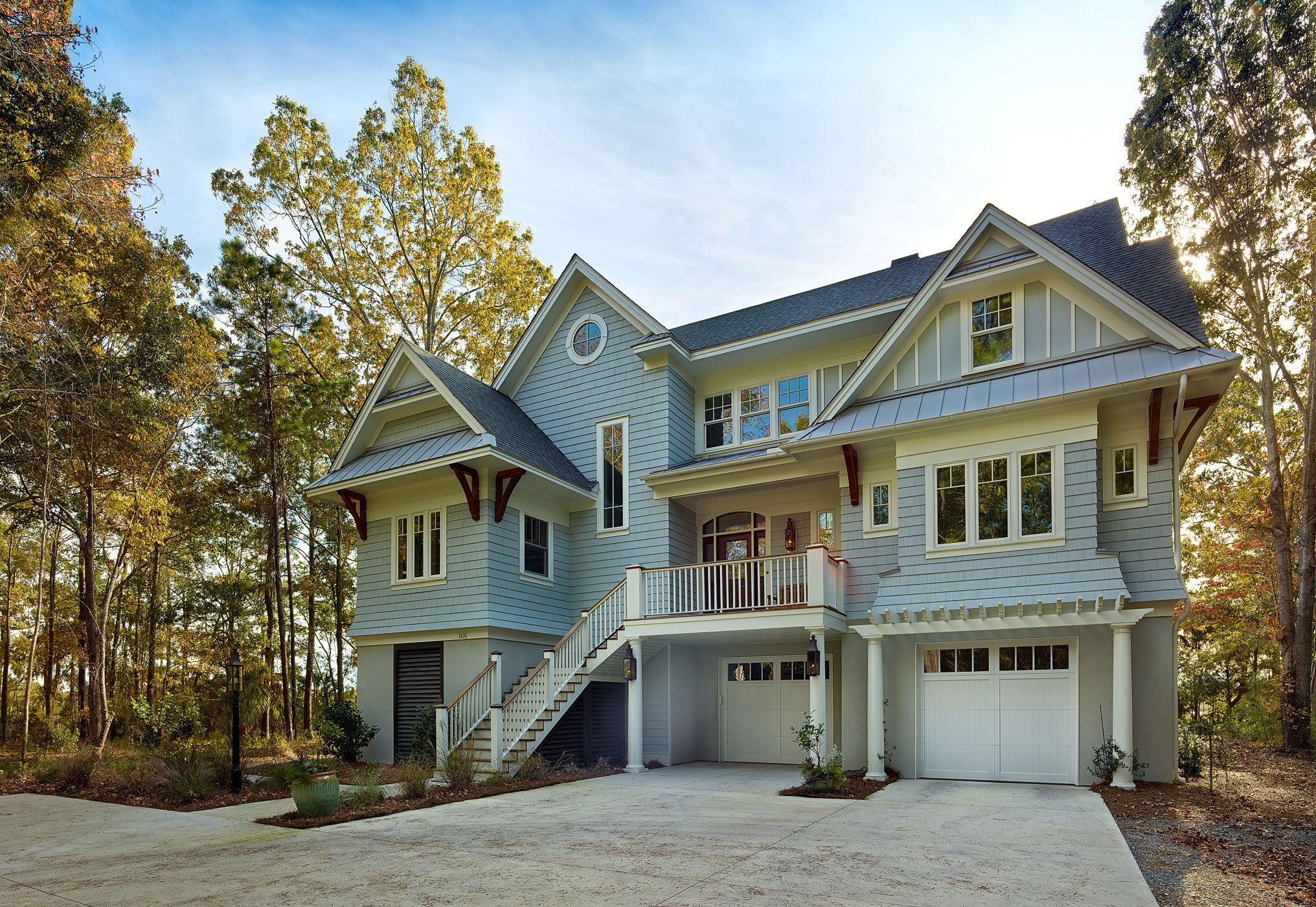 Standing brightly apart from its wooded surroundings, the tall home stands elevated above a concrete foundation with two garage stalls beneath the main body. Front entrance stands on a balcony wrapped in white and natural wood railings.